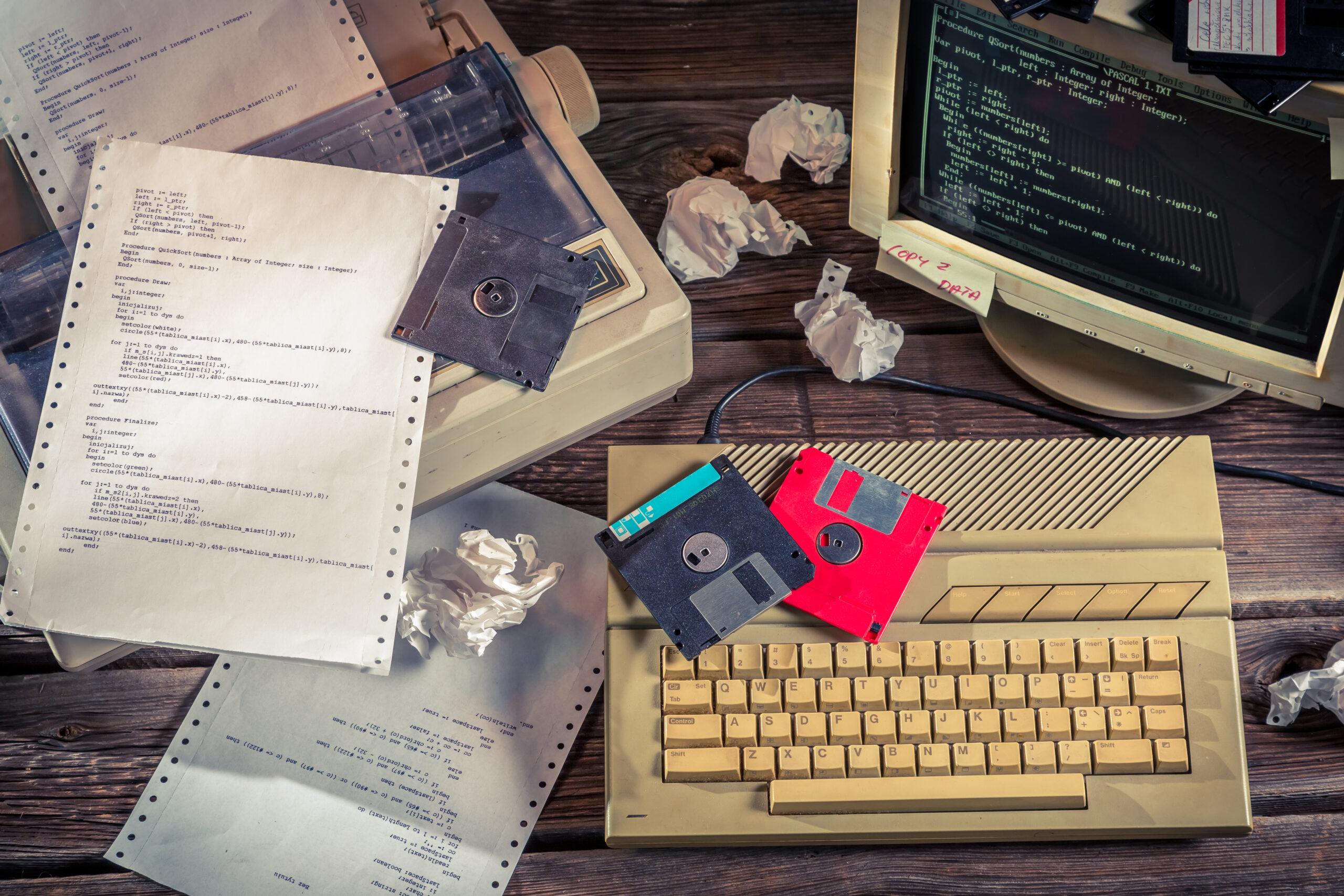 Vanha työpöytä, jossa vanha tietokone, sekä romppuja