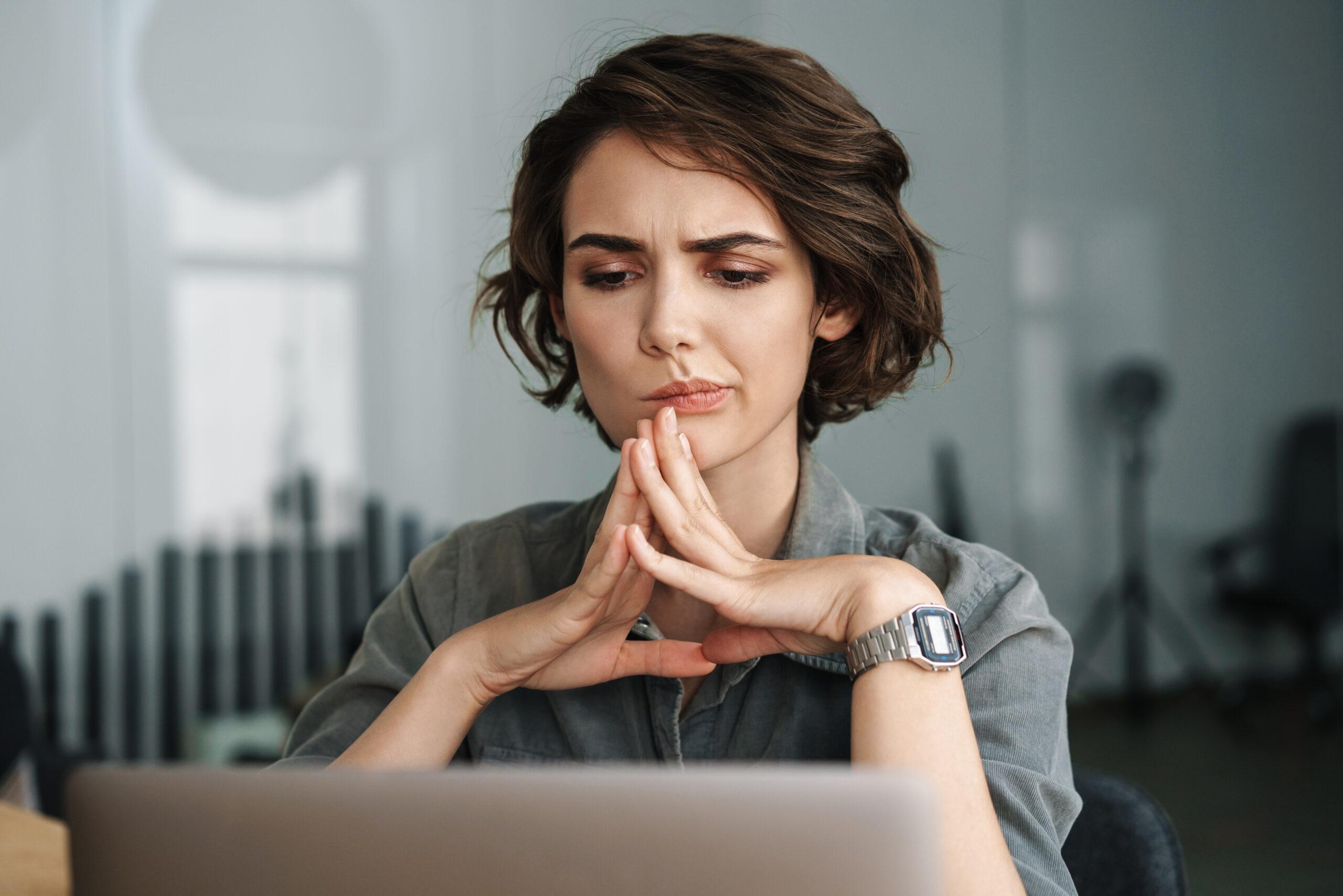 pohdiskeleva tummahiuksinen nainen istuu tietokoneen ääressä
