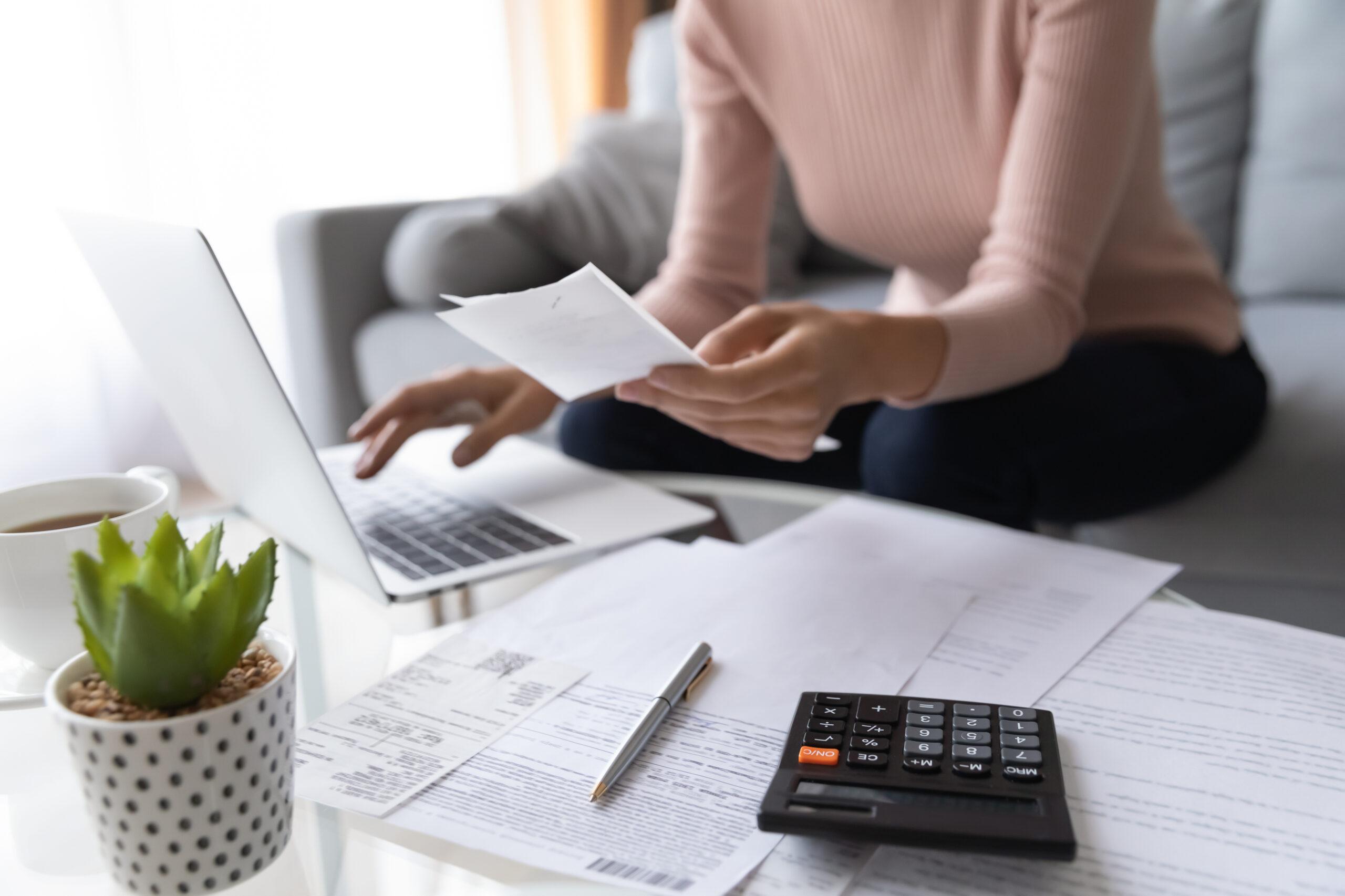 Nainen beigessä paidassa istuu näpyttämässä tietokonetta ja pitää kädessään paperia. Etualalla pöydällä myös taskulaskin, papereita ja kuulakärkikynä