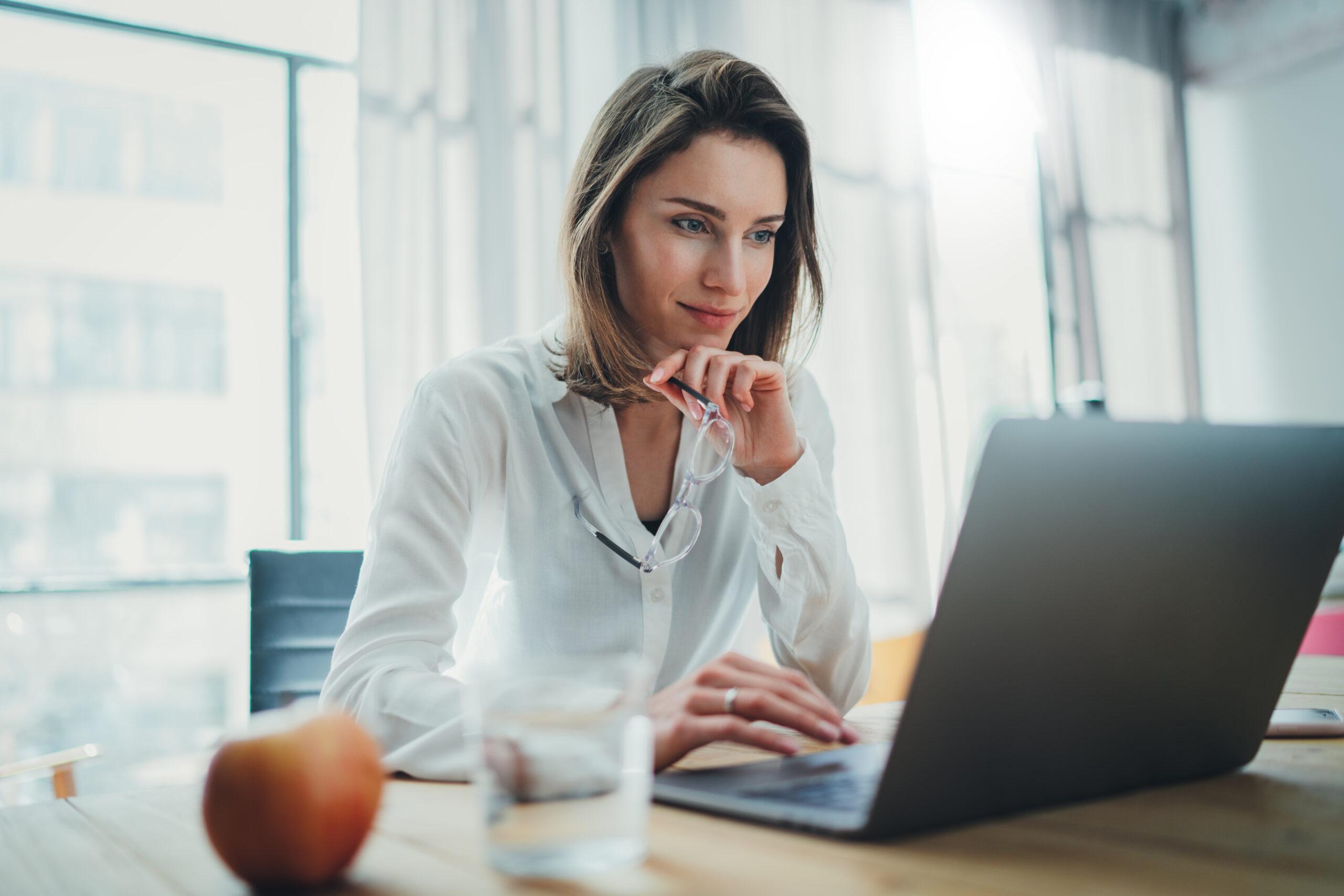 Nainen valkoisessa kauluspaidassa istuu kannettavan tietokoneen ääressä mietteliäänä. Etualalla on vesilasi ja omena